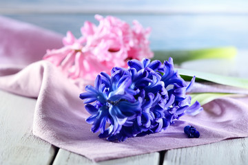 Beautiful hyacinth flowers on wooden table with napkin, closeup