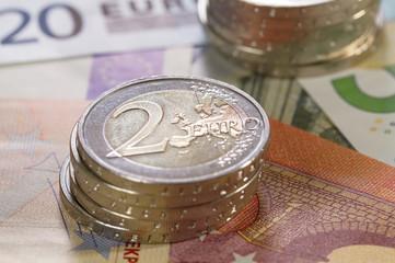Geldscheine liegend mit zwei Stapeln 2 Euro Münzen