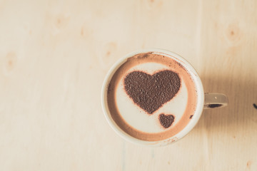 Heart shape on coffee cup on wooden background with vintage colo