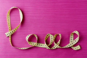 Love word formed with measuring tape on purple background