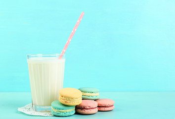 Assortment of gentle colorful macaroons and glass with milk