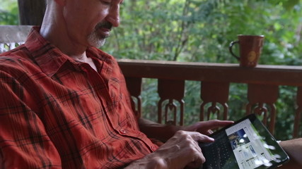 old man wonders at news in tablet PC
