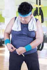 Overweight man measure his belly at gym