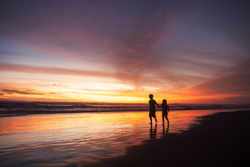 Playful children on beach at sunset time