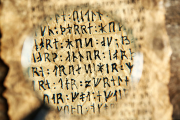 Grunge paper with hieroglyphics with magnifier close up