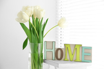Home in colorful letters and spring flowers in light white