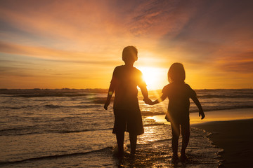 Two children holding hands at beach