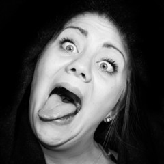 crazy woman with staring eyes and outstretched tongue