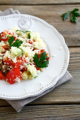 Salad with couscous and fresh vegetables on the white plate