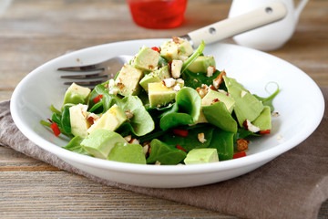 Salad with avocado and spinach in a white bowl