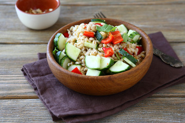 Pearl barley salad with vegetables in a wooden bowl