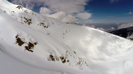 AERIAL: Flight over mountain covered with snow  - winter