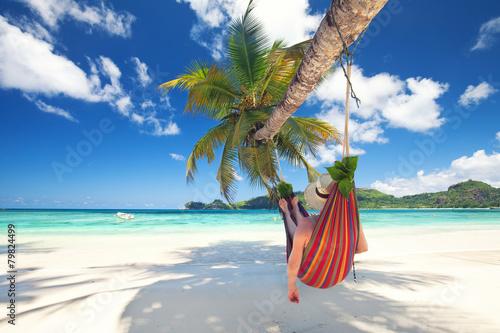 Frau liegt in der Hängematte am Strand - 79824499