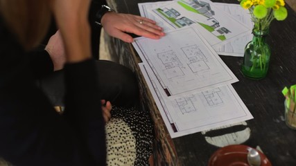 Young couple looking at new home drawings at coffee shop