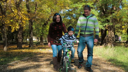 Happy Young Family With a Child On Bike Walking In Autumn Park