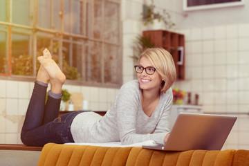 entspannte frau liegt mit laptop auf dem sofa