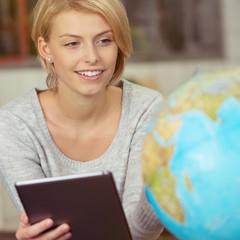 junge frau mit tablet und globus