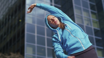 Hooded athlete warming up before a run in the city