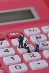 電卓の上でパソコンをしているサラリーマンと警察官