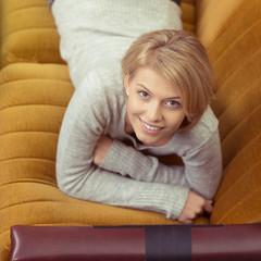 attraktive frau liegt auf dem sofa und schaut hoch