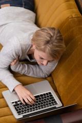 frau liegt auf dem sofa und tippt am laptop