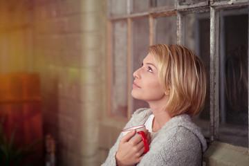 blonde frau lehnt am fenster und schaut nach oben