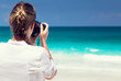 woman on tropical beach taking photo with mirrorless camera