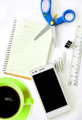 Coffee, paperclip, notebook, eyeglasses and earphone