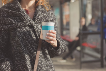 Woman with cup of coffee at bus stop