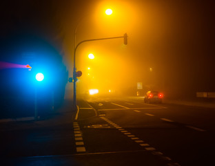Illuminated city crossroads at night in fog with cars.