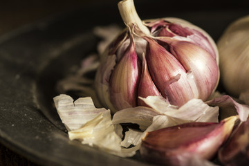 Fresh garlic cloves in moody natural lighting set up with vintag