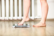 Caucasian female legs gently tread on the floor scales - 79835612