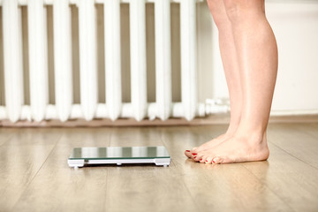 Human legs standing near floor weight scale for weighing