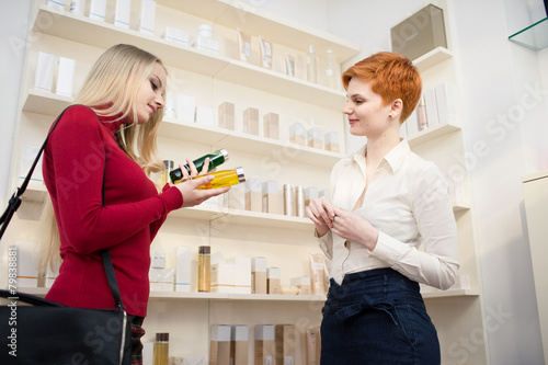 Young woman comparing products with saleswoman - 79838881