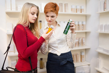 Young woman comparing products with saleswoman