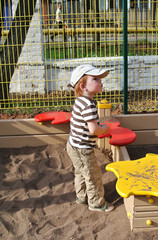 Little boy playing in sandpit in the park