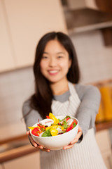 asian smiling woman is holding a colorful salad in her hands