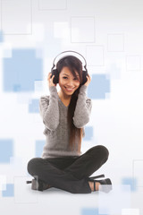 Asian woman is listening music with headphones