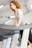 Woman doing workout on a treadmill while smiling
