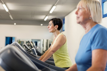 Two mature women are running on a treadmill