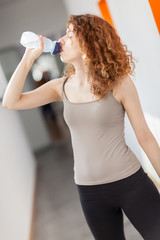 woman drinks water from a bottle in the gym