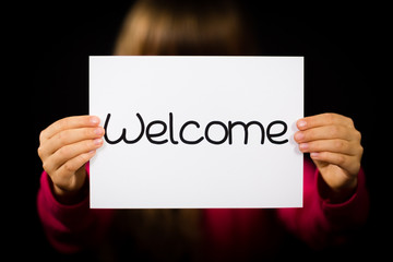 Child holding Welcome sign