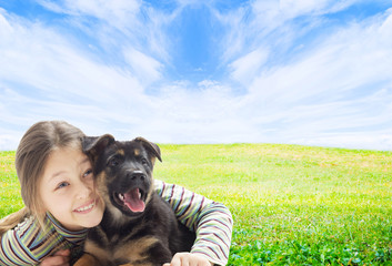 positive kid with a puppy on a green lawn
