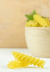 Spiral shaped pasta pieces and bowl with copy space