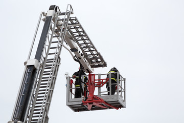Firefighters at firetrack escape ladder during accident fighting
