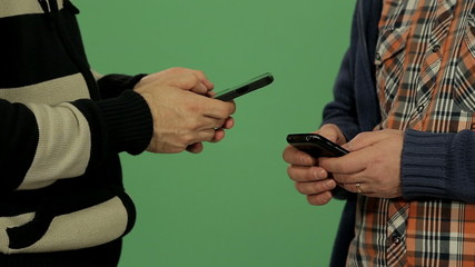 Two men using smartphone with green screen background