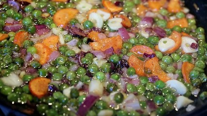 green peas and carrots, garlic and onion fried in a pan