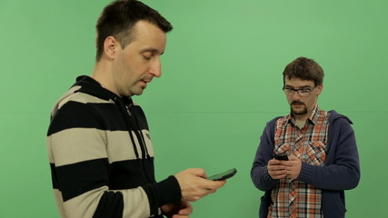 Two men withe mobile phones on the green screen background