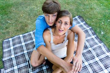 Paar sitzt umarmt auf Park Wiese