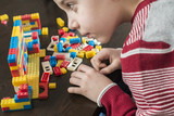 Fototapety Child play with children's constructor toys
